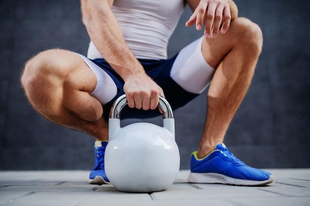 Uomo muscolare sportivo caucasico che posa, che si accovaccia e che tiene la campana del bollitore all'aperto.