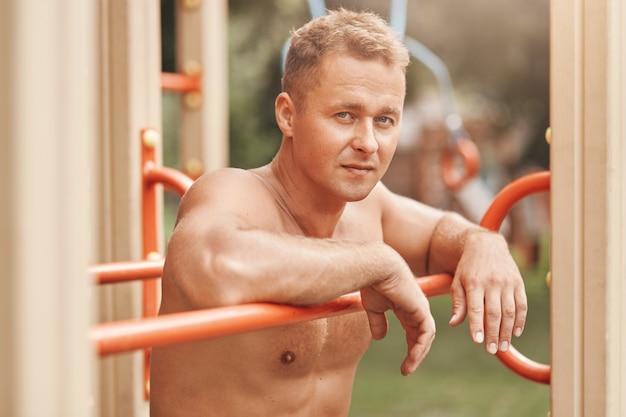 Uomo muscoloso a torso nudo dall'aspetto accattivante, posa all'aperto sul campo sportivo, ama l'allenamento di strada