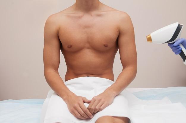 Uomo muscoloso atleta con pelle liscia e chiara. epilazione e depilazione dei capelli nel salone di bellezza. concetto di depilazione laser maschile. estetista che utilizza apparati moderni per le procedure. cura della pelle e della bellezza