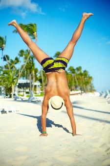 Uomo muscoloso bello felice in cappellino da sole sulla spiaggia che salta dietro il cielo blu dietro il cielo blu