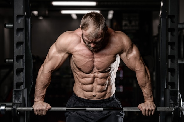 Uomo muscoloso brutale con stile di vita di salute di modello di fitness con la barba lunga barba