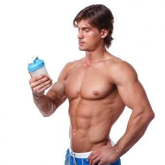 Uomo muscoloso con bevanda proteica in shaker