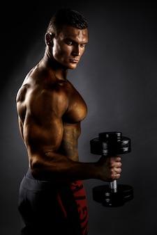 Uomo muscoloso con manubri. vista laterale. sfondo nero
