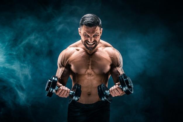 Uomo muscoloso con manubri