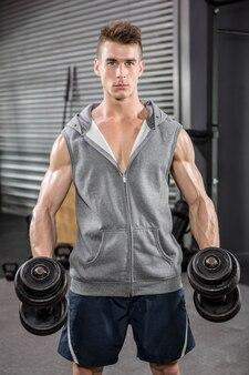 Uomo muscoloso con ponticello grigio che tiene i dumbbells in palestra