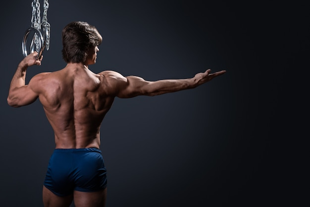 Uomo muscoloso e anelli metallici