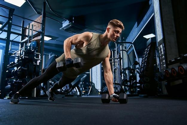 Uomo muscoloso facendo push up da un lato.