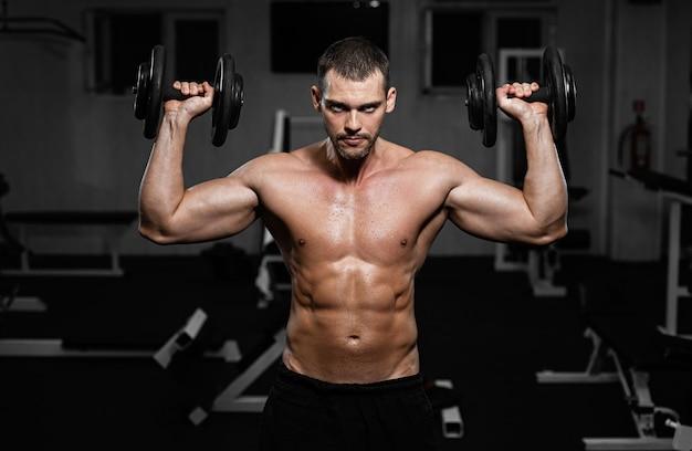 Uomo muscoloso in allenamento in palestra con i manubri, il ragazzo pompa il suo muscolo deltoide