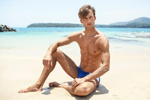 Uomo muscoloso in pantaloncini blu pone una spiaggia rivista. vacanza tropicale