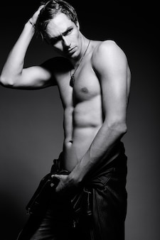 Uomo muscoloso modello maschio giovane bello muscoloso in posa in studio che mostra i suoi muscoli addominali in giacca di pelle