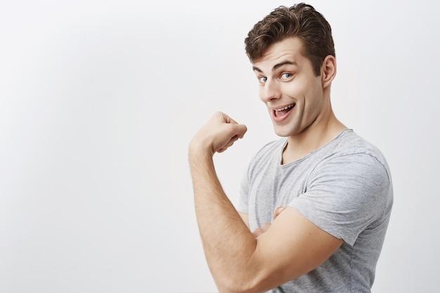Uomo muscoloso positivo vestito con indifferenza, mostra i bicipiti dopo l'allenamento in palestra, dimostrando quanto sia bello. scherzando, facendo facce il maschio caucasico si vanta della sua forza, come dire guardalo