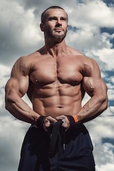 Uomo muscoloso sotto il cielo nuvoloso