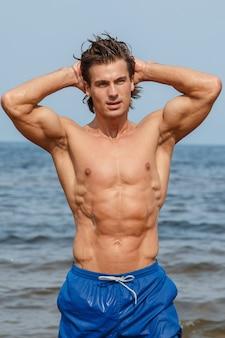 Uomo muscoloso sulla spiaggia