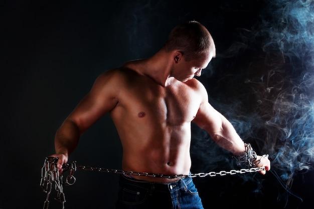 Uomo muscoloso torso nudo con catene di metallo