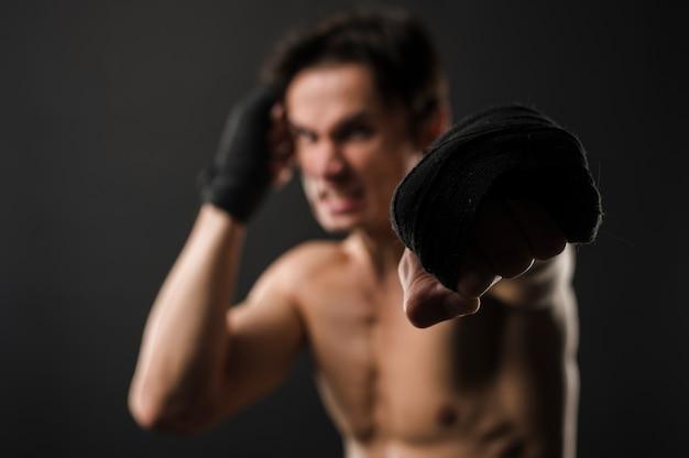 Uomo muscoloso torso nudo sfocato con guantoni da boxe