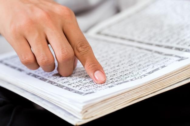 Uomo musulmano asiatico che studia corano o corano