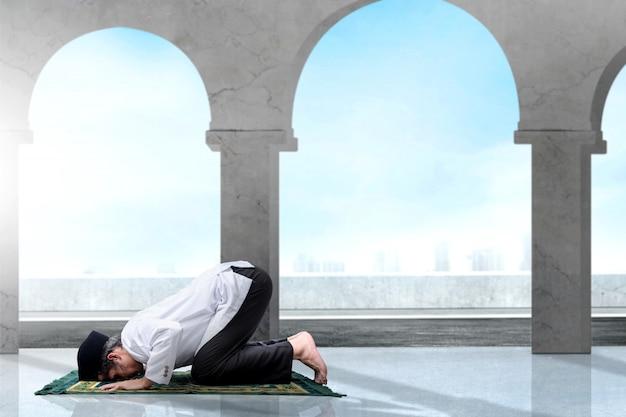 Uomo musulmano asiatico con un tappeto da preghiera in posizione di preghiera (salat)
