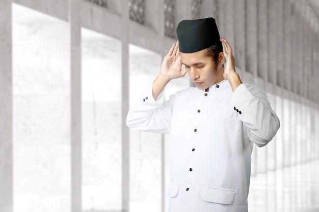 Uomo musulmano asiatico in posizione di preghiera (salat)