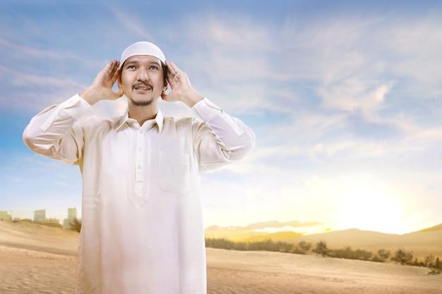Uomo musulmano asiatico sorridente con il cappuccio che sta e che prega sulla sabbia
