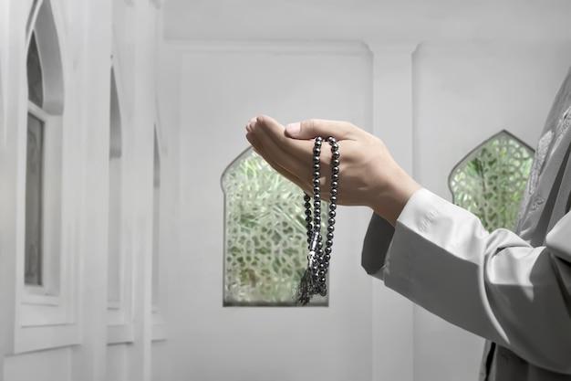 Uomo musulmano che alza la mano e prega per dio
