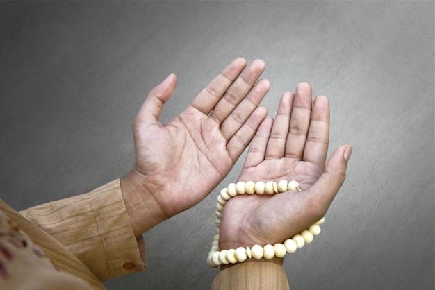 Uomo musulmano che prega con i branelli di preghiera