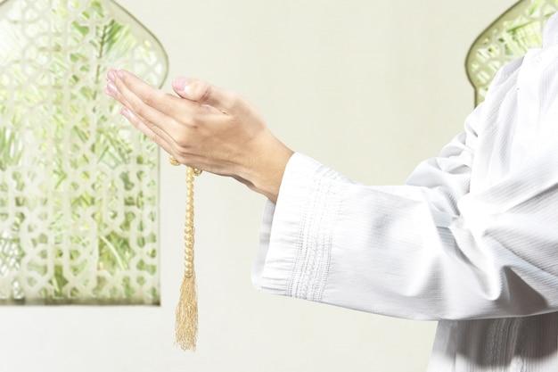 Uomo musulmano che prega con le perle di preghiera sulle sue mani