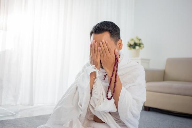 Uomo musulmano che prega in vestiti tradizionali bianchi