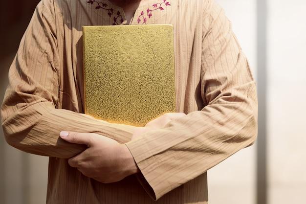 Uomo musulmano che tiene il corano