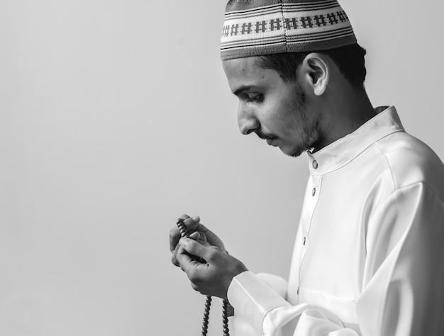 Uomo musulmano che usa misbaha per tenere traccia del conteggio in tasbih