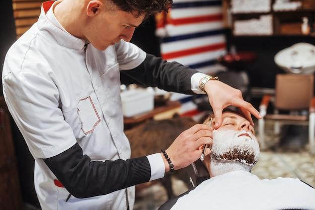 Uomo nel barbiere tagliatore di barba