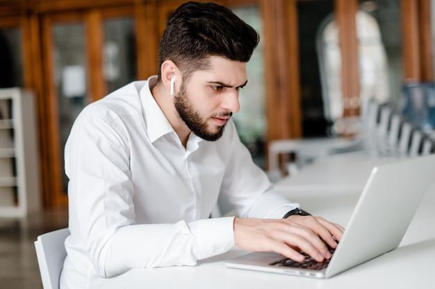 Uomo nel luogo di lavoro con il computer portatile in ufficio