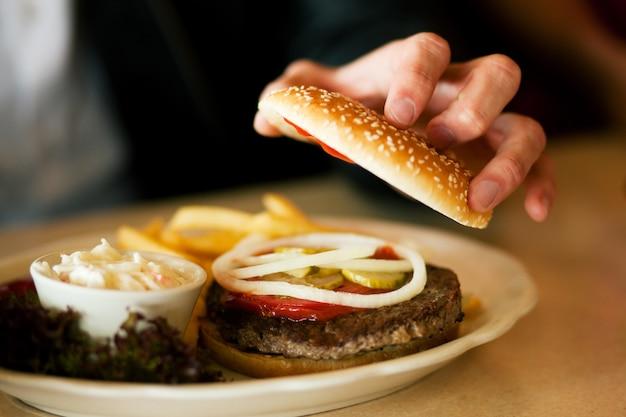 Uomo nel ristorante che mangia hamburger