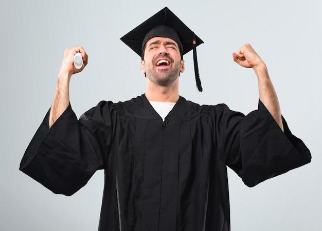 Uomo nel suo giorno di laurea università celebra una vittoria nella posizione del vincitore su sfondo grigio