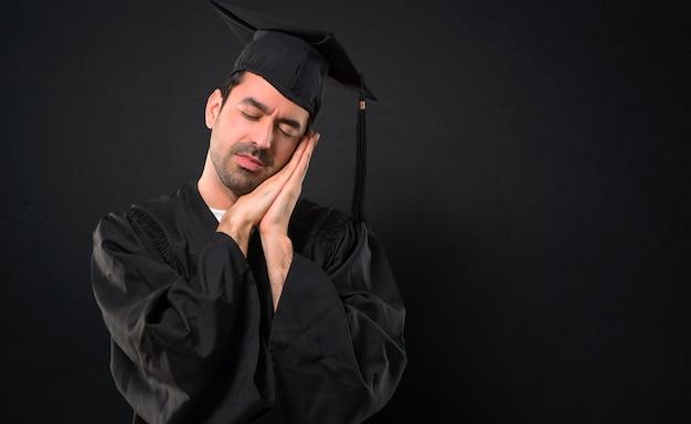 Uomo nel suo giorno di laurea università facendo il gesto del sonno. espressione adorabile e dolce