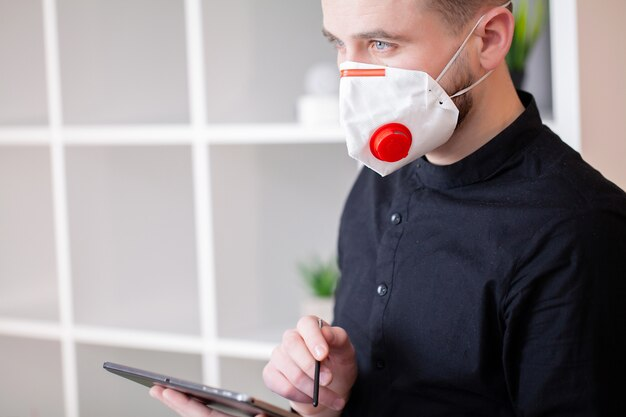 Uomo nella maschera protettiva che lavora alla compressa in ufficio
