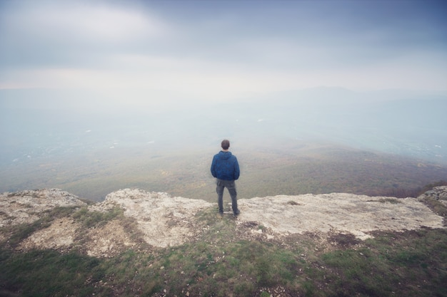 Uomo nella nebbia in montagna