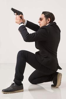 Uomo nella serie di affari e pistola su fondo bianco, sparando e sedendosi sul fondo bianco