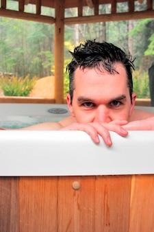 Uomo nella vasca idromassaggio all'aperto