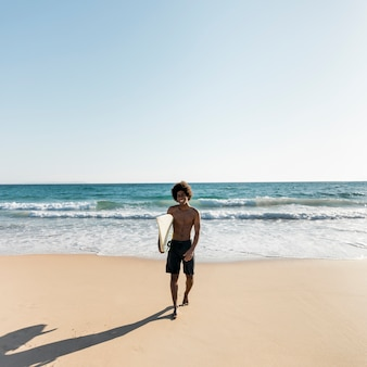 Uomo nero che esce dall'oceano dopo aver surfato