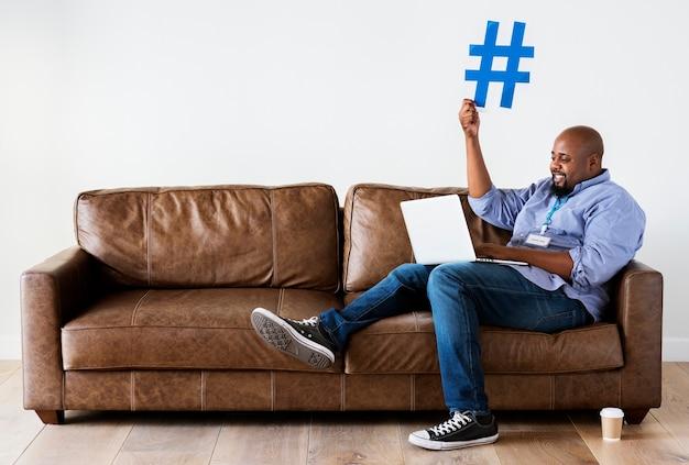 Uomo nero che lavora al computer portatile
