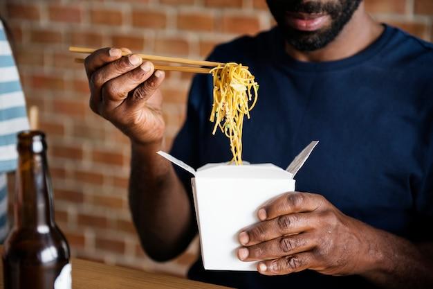 Uomo nero che mangia chow mein