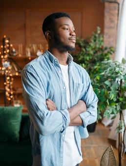 Uomo nero con uno sguardo furbo in salotto, relax a casa. persona maschio giovane afroamericano in piedi nella sua casa
