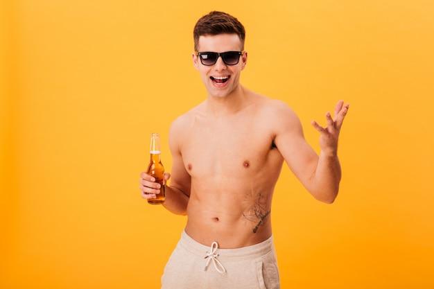 Uomo nudo allegro in pantaloncini e occhiali da sole tenendo la bottiglia di birra