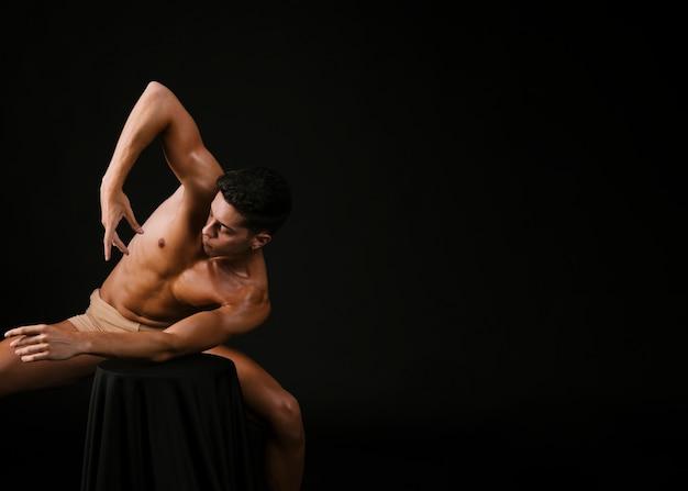 Uomo nudo che si appoggia con il gomito sulla sedia e alzando la mano