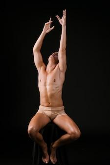 Uomo nudo che si estende con entrambe le mani