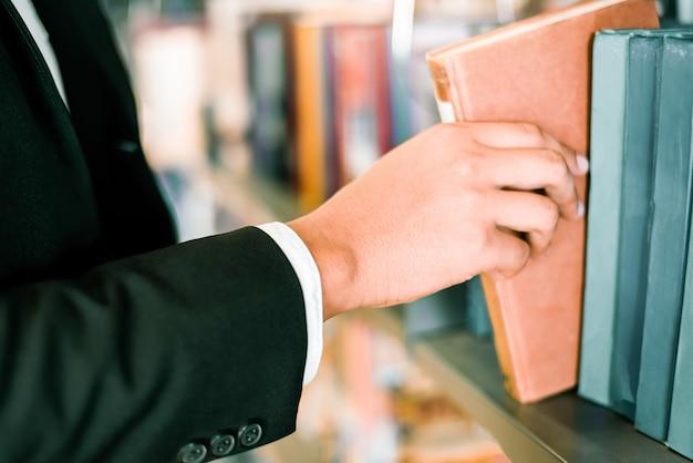 Uomo o studente di affari che tiene un libro a portata di mano o che seleziona un libro sullo scaffale per libri sullo sfondo degli scaffali per libri della biblioteca - business education study concept