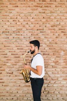 Uomo obliquo che gioca il sax con il fondo del muro di mattoni