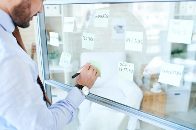 Uomo organizzando adesivi e facendo piano
