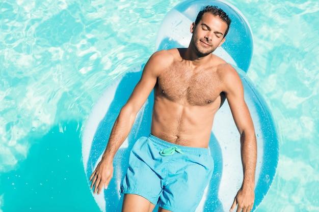 Uomo pacifico sul lilo in piscina