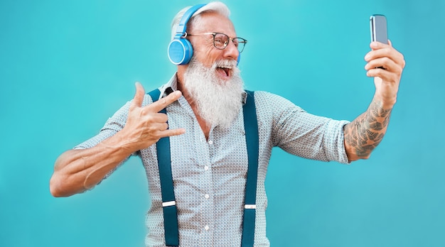 Uomo pazzo senior che utilizza l'app per smartphone per creare playlist con musica rock - tatuaggio alla moda che si diverte con la tecnologia del telefono cellulare - tecnologia e concetto di stile di vita anziano gioioso - focus on face